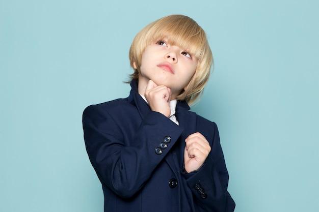 Вид спереди милый деловой мальчик в синем классическом костюме позирует мечтательно мыслящей деловой работе моды