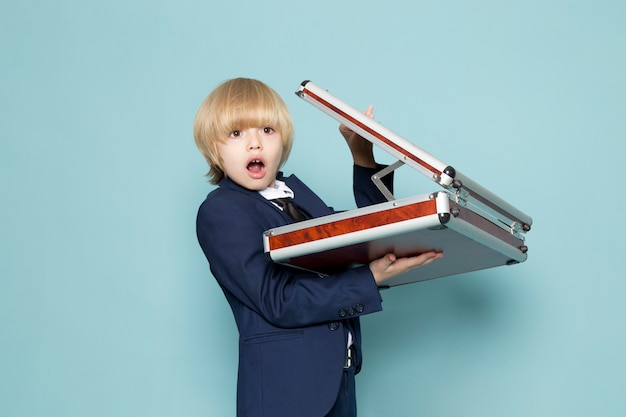 Вид спереди симпатичного делового мальчика в синем классическом костюме, позирующего с коричнево-серебряным чемоданом, удивленной деловой работой.