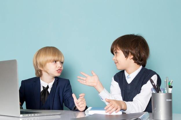 Вид спереди милый бизнес-мальчик в синем классическом костюме позирует перед серебряным ноутбуком вместе с другим парнем, обсуждающим рабочую моду