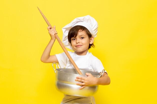 Вид спереди милый маленький ребенок в белом кухонном костюме и белой кепке, держащей серебряную сковороду и скалку, улыбающейся на желтой стене, ребенок готовит кухню еду