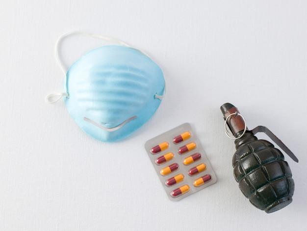 Респираторные таблетки с гранатово-голубой маской против ковидного, а также вишнево-оранжевые таблетки и темно-зеленая ручная граната на белом полу