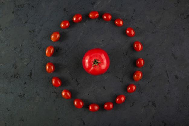 灰色の机の上のチェリートマトの赤い完熟トマト