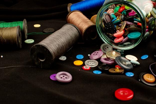 Нитки и пуговицы из разноцветной пластиковой винтажной композиции на коричневой ткани