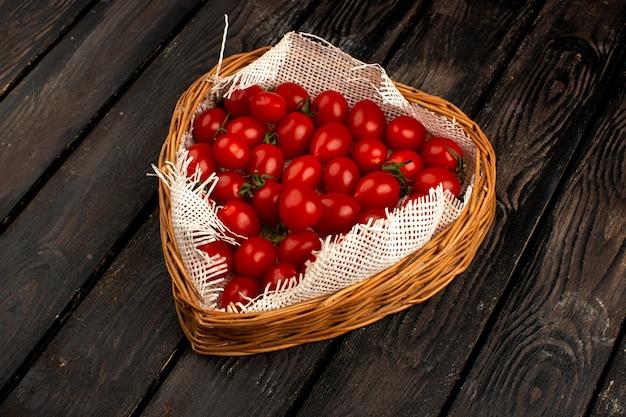 茶色の木製のバスケットの中に熟したトマト赤
