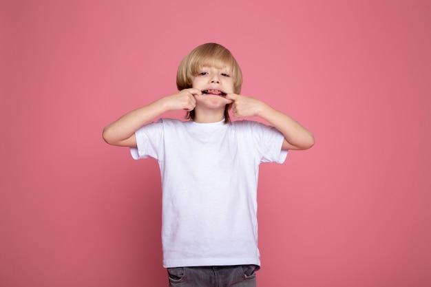 Милый мальчик, делая смешные выражения лица в белой футболке и серых джинсах портрет милого очаровательного ребенка мальчика на розовом столе