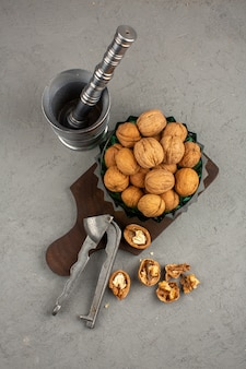 クルミは、灰色の机の上の金属製の工具とともに、茶色の全体と皮をむいたナッツの上面図