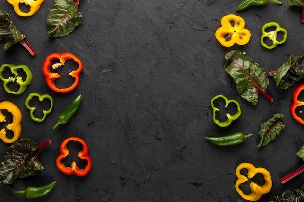 Цветные овощи свежие спелые и нарезанные на темный стол