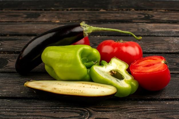 Красочные овощи свежие спелые половинки красных помидоров зеленые перцы и черные баклажаны на коричневом деревянном деревенском столе