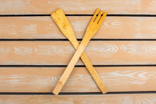Скрещенные кухонные инструменты деревянные сделаны на ярком фоне