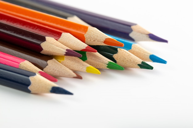 Цветные карандаши разноцветные для рисования выложены на белой стене