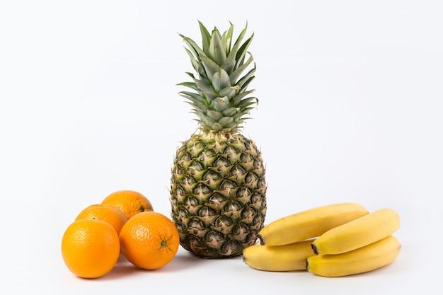 Разные фрукты, богатые витаминами, спелые цельные ананасовые апельсины и бананы, изолированные на белом полу