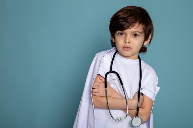Маленький мальчик мило очаровательны в белом медицинском костюме, глядя на камеру на синем