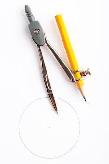 金属コンパスは白い机の上の鉛筆でトップビューを分離