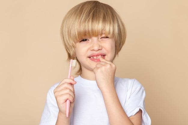 ピンクの机の上の歯ブラシを保持している金髪のかわいい男の子の甘い