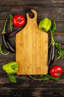 素朴な木製の机の上の緑のハーブと一緒に熟したビタミンが豊富な黒ナス赤トマトと緑のピーマンの新鮮な野菜のトップビュー