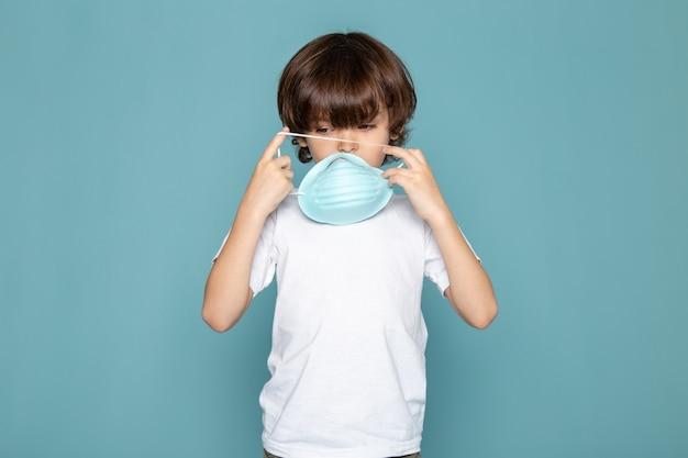 Закрыть, посмотреть ребенок мальчик сладкий в белой футболке в синей респираторной защитной стерильной маске в белой футболке на синем фоне