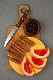 グレーの床に茶色の木製の机の上の黄色のプレート内のグレープフルーツシナモンコーヒー