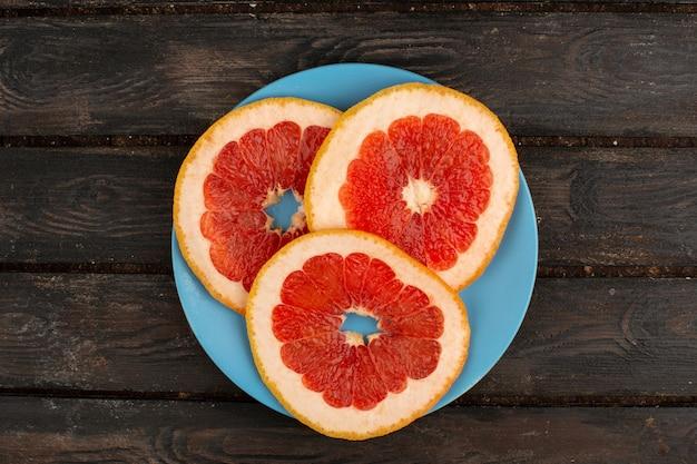 グレープフルーツリングブループレート内と素朴な木の床にオレンジ色のパルプジューシーなまろやか