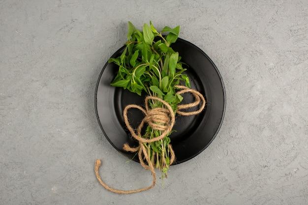 Зеленые травы внутри черной пластины на сером