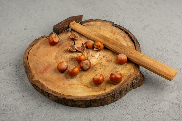 Молоток фундука на коричневом столе и сером поле
