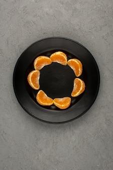 オレンジ色のみかんは、灰色の机の上の黒い皿に熟したジューシーな熟したトップビューをスライス