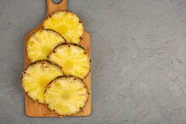 Ломтики ананаса выложены сочными свежими на коричневом деревянном столе и сером фоне