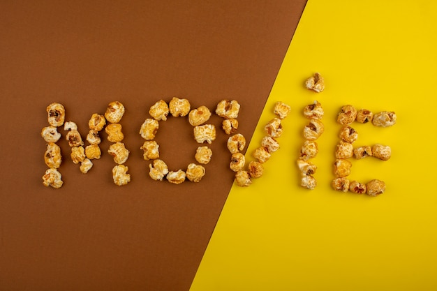 黄褐色の机の上の甘いポップコーンで形作られたポップコーン映画の言葉