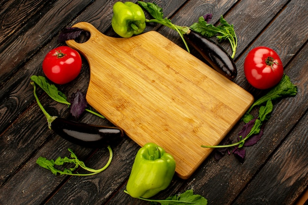 Красные помидоры свежие спелые с зеленым перцем и черными баклажанами вместе с зеленью и коричневым столом на деревянном полу