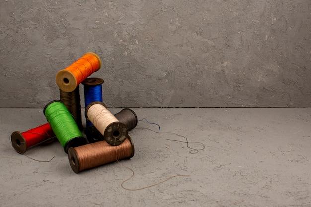 灰色の机の上に色とりどりのミシン糸