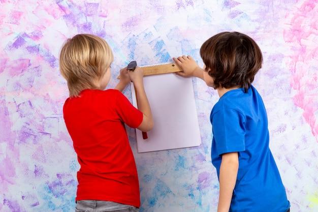 Вид сзади мальчиков, работающих с молотком в красных и синих футболках на разноцветной стене