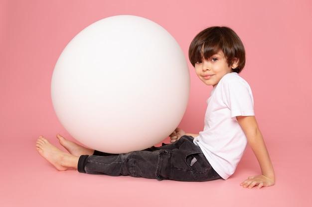 Вид спереди прелестный мальчик в белой футболке играет с белым круглым мячом на розовом столе