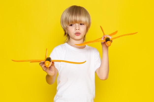 黄色の机の上のオレンジ色のおもちゃの飛行機を保持している正面金髪男