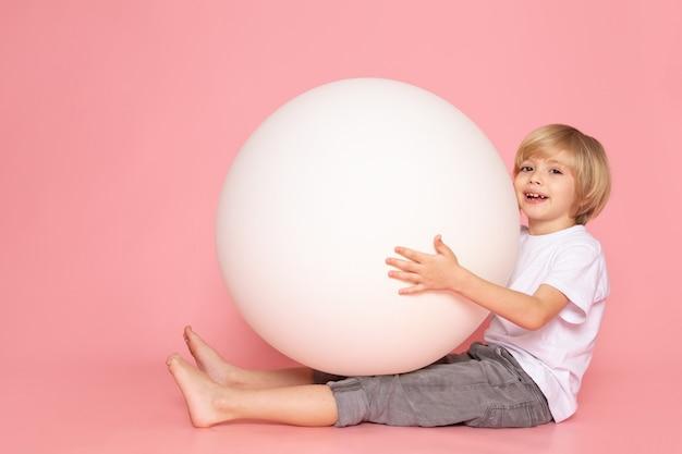 Вид спереди блондинка счастливый мальчик играет с белым мячом в белой футболке на розовом полу