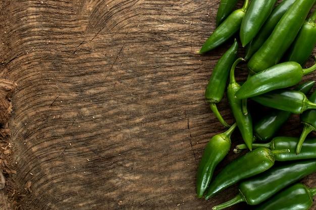 Пряный зеленый перец на деревянном фоне
