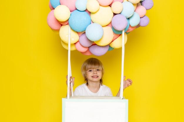 Вид спереди белокурый малыш в белой футболке вместе с разноцветными воздушными шариками на желтом