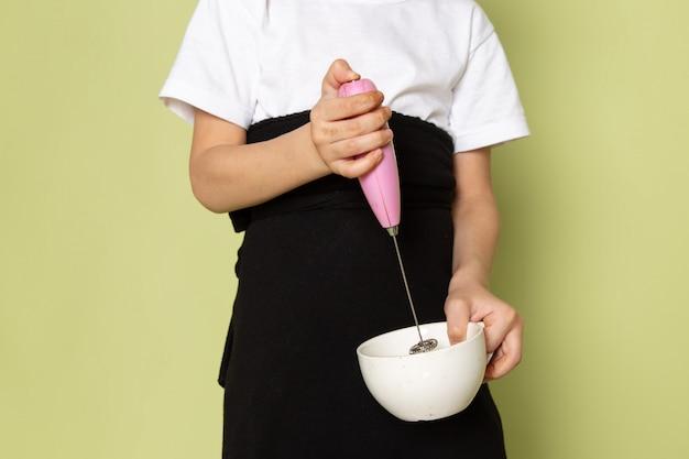 Вид спереди милый мальчик в белой футболке готовит кофе внутри белой тарелке на каменном цветном пространстве