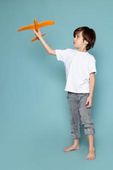 Вид спереди ребенок мальчик в белой футболке держит игрушку оранжевого самолета на синем
