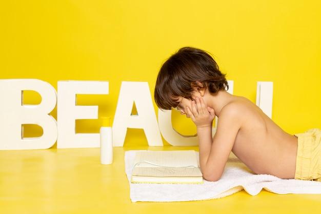 Вид спереди ребенок мальчик сидит на белом полотенце вместе со словом пляж на желтом столе