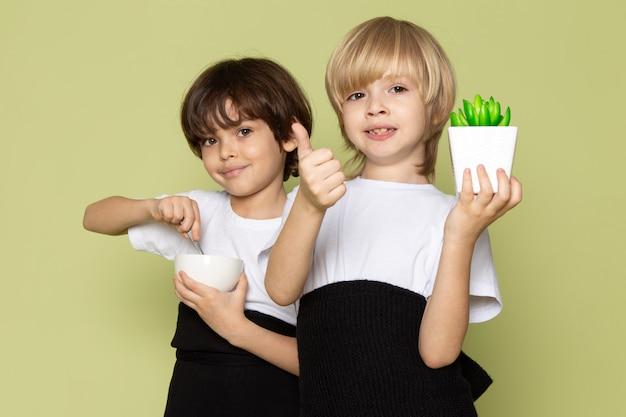 Пара вид спереди мальчиков, улыбаясь, держа зеленый маленький завод и кофе