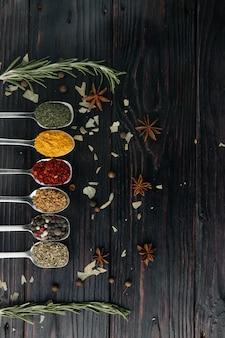 上からの眺め。インド料理。調味料。スパイス入り金属スプーン。コピー用の空き容量