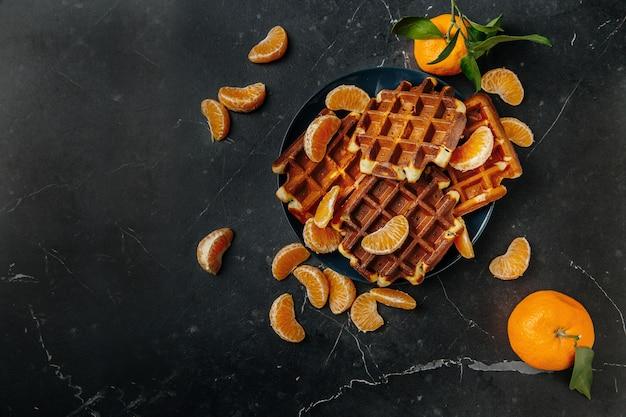 Мягкие венские вафли на тарелке с мандаринами