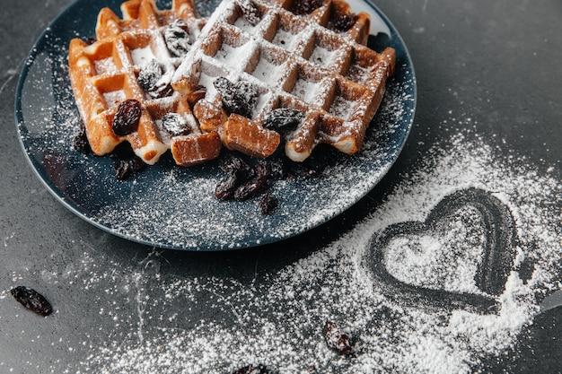 ウィーンのワッフル、粉砂糖を振りかけ、暗いテクスチャテーブル