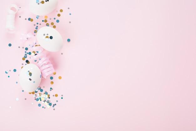 Белые яйца на розовом фоне, праздничные блестки, с копией пространства. пасхальная концепция.