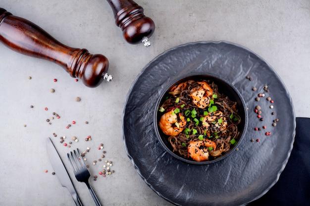 灰色の背景に、エンドウ豆で飾られた黒い皿にエビと中華鍋麺。アジア料理のコンセプト。