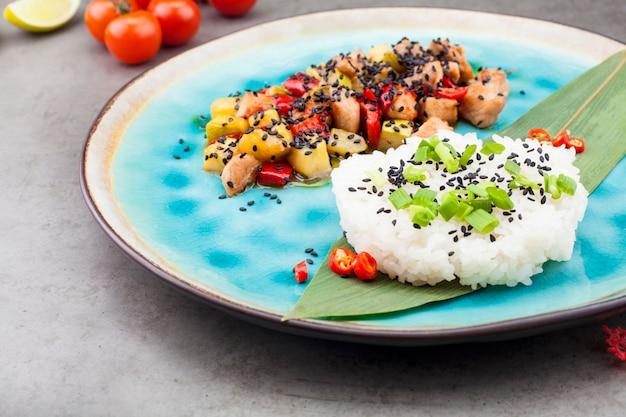 Рисотто, рис подается на пальмовых листьях рядом с начинкой из овощей и мяса, на сером фоне, рядом с ломтиками лайма и помидорами черри. концепция рецептов или меню
