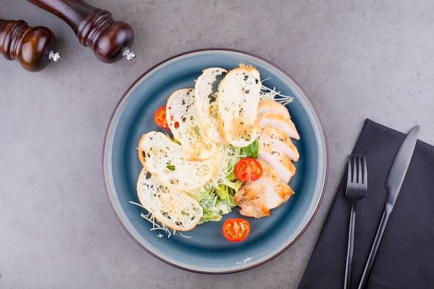 Салат цезарь с курицей, украшенный помидорами черри, на сером столе. концепция меню ресторана или здорового питания.