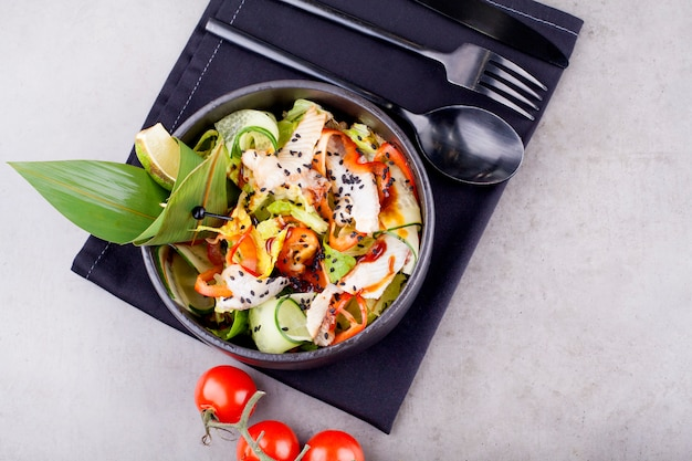 Салат с копченым угрем, украшенный большим зеленым листом, в черной тарелке. концепция азиатской кухни или меню для ресторана.