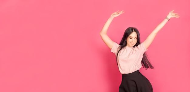 女性はピンクの背景に、喜びの感情を込めて、コピースペースで踊っています。パーティーやお祝いのコンセプトです。