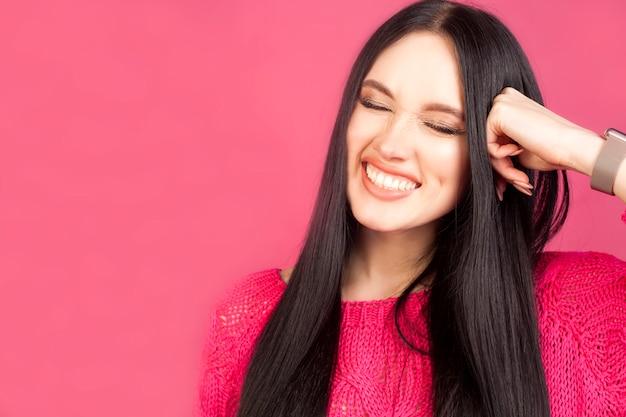 女性はピンクの背景に目を閉じて、広く笑っています。幸福、喜び、ポジティブの感情の概念。