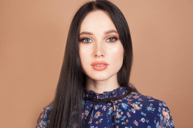 青い目と青いドレスのモデル、美しいブルネットの女性の肖像画。女性の美しさの概念。